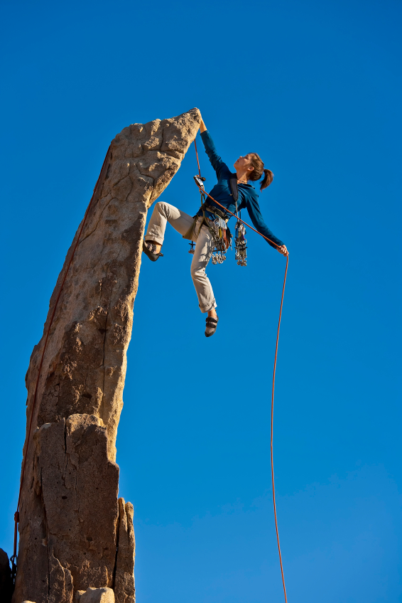 Female rock climber reaching the summit.