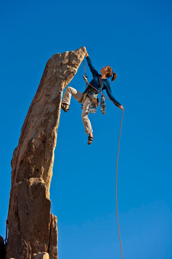 Female rock climber reaching the summit.
